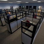 """Workers assemble, arrange and install new furniture in a empty office."""