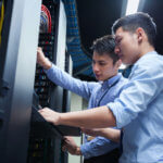 Young IT engineers inspecting data center servers.
